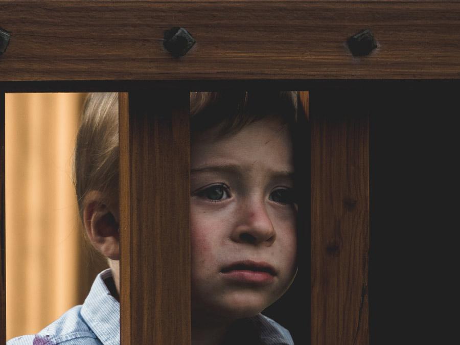 Smutny chłopiec spogląda przez szczeble drewnianego ogrodzenia /Ilustracja do tekstu: Nieudane adopcje. Rozmowa z dyrektor ośrodka preadopcyjnego w Otwocku