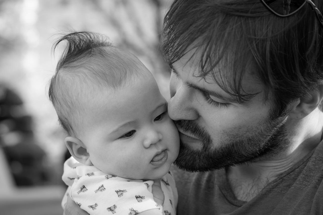Młody tata przytula dziecko /Ilustracja do tekstu: Dzień ojca /Chemioterapia w dzieciństwie a męska płodność. Nowa strategia zachowania płodności po raku już wkrótce?