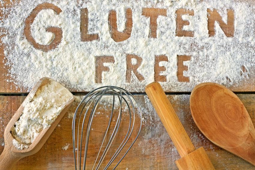 """przybory kuchenne i rozsypana mąka, na której zapisano palcem napis """"gluten free"""""""