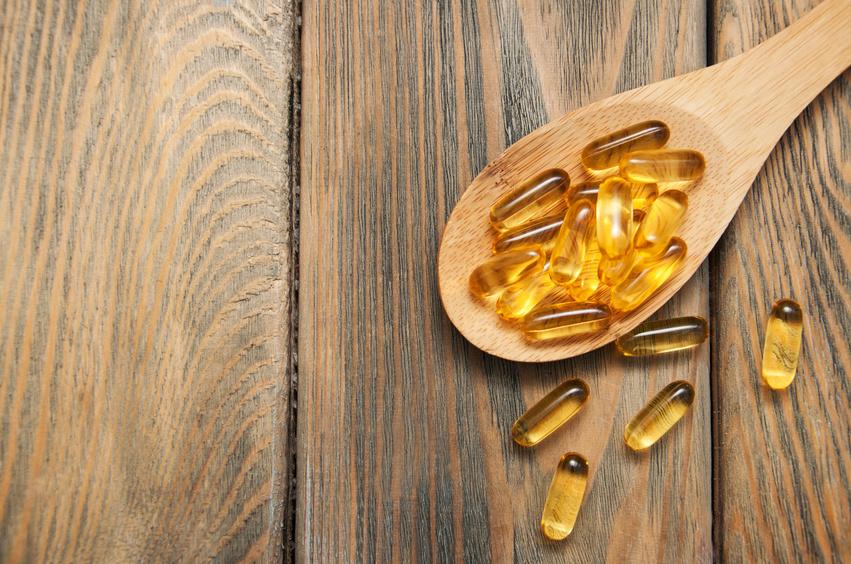 Preparat z witaminą D w kapsułkach na drewnianej łyżce na drewnianej desce. Ilustracja do tekstu: Suplementacja witaminy D przed ciążą. Postępowanie w przypadku niedoborów witaminy D. Witamina D