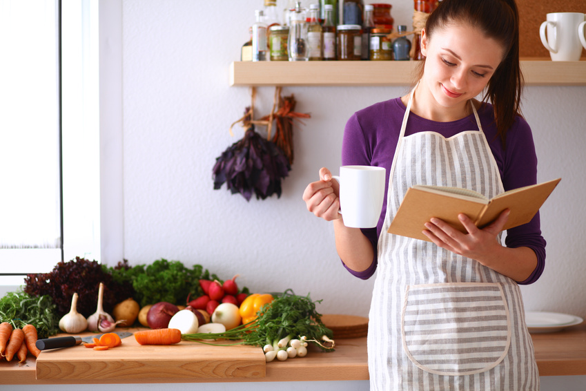 Kobieta w kuchni; czyta książkę kucharską z kubkiem w dłoni /Ilustracja do: Naturalne leczenie PCOS: 6 sposobów