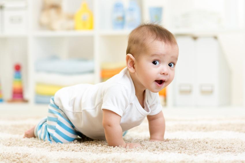 Raczkujące uśmiechnięte niemowlę /Ilustracja do tekstu: Koszt wychowania dziecka porównywalny do zakupu mieszkania. te liczby szokują