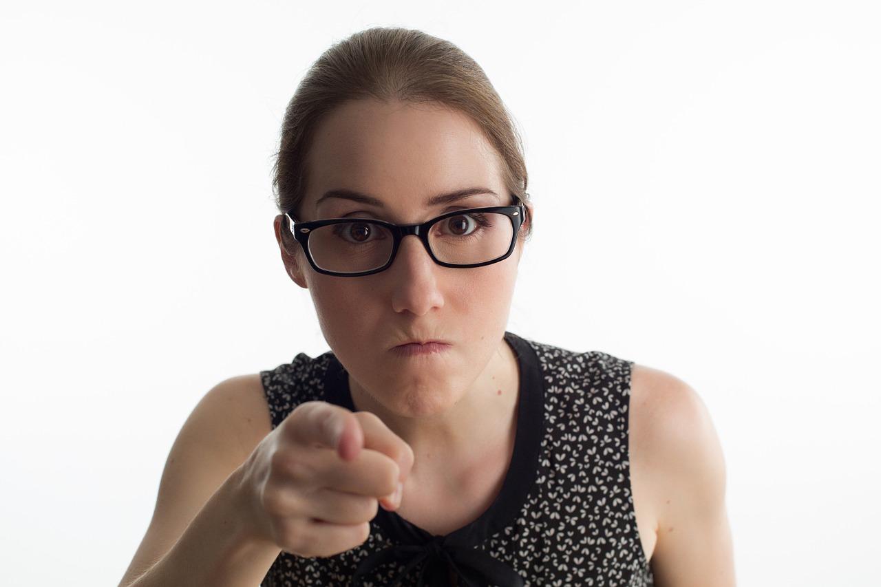 """8 odpowiedzi na pytania: """"Kiedy dziecko"""" /Na zdjęciu: Zdenerowwana kobieta w okularach wskazuje palcem prosto w obiektyw"""