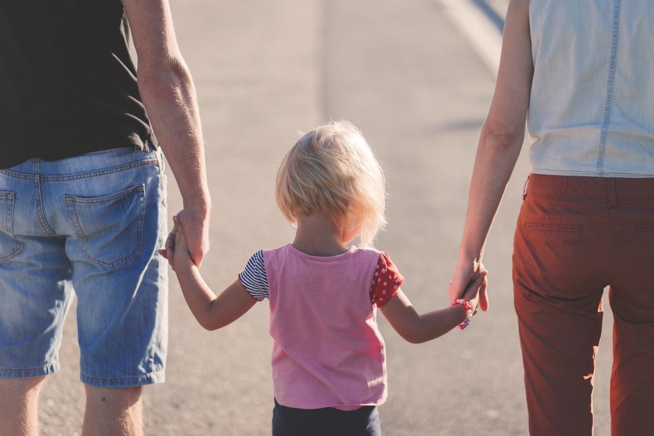 Dziecko idzie za rękę z rodzicami