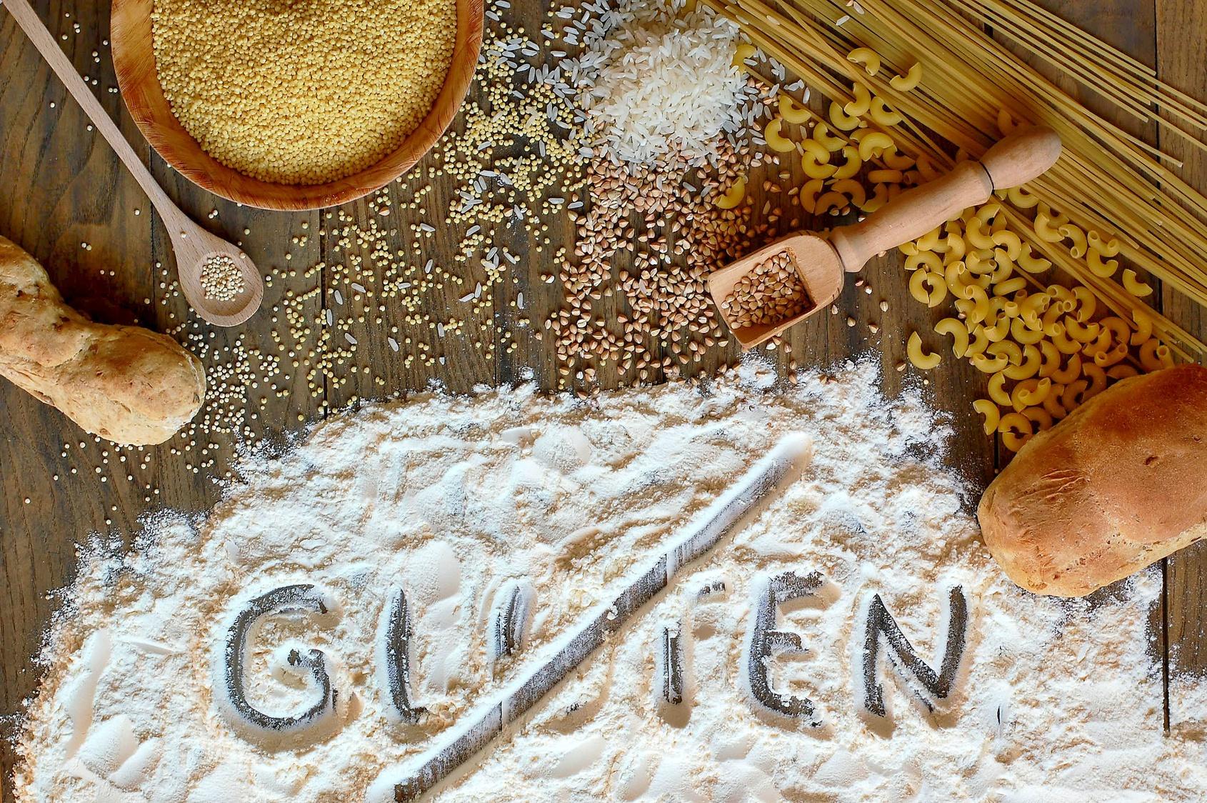 """produkty spożywcze i rozsypana mąka, na której widnieje przekreślony napis """"Gluten"""""""