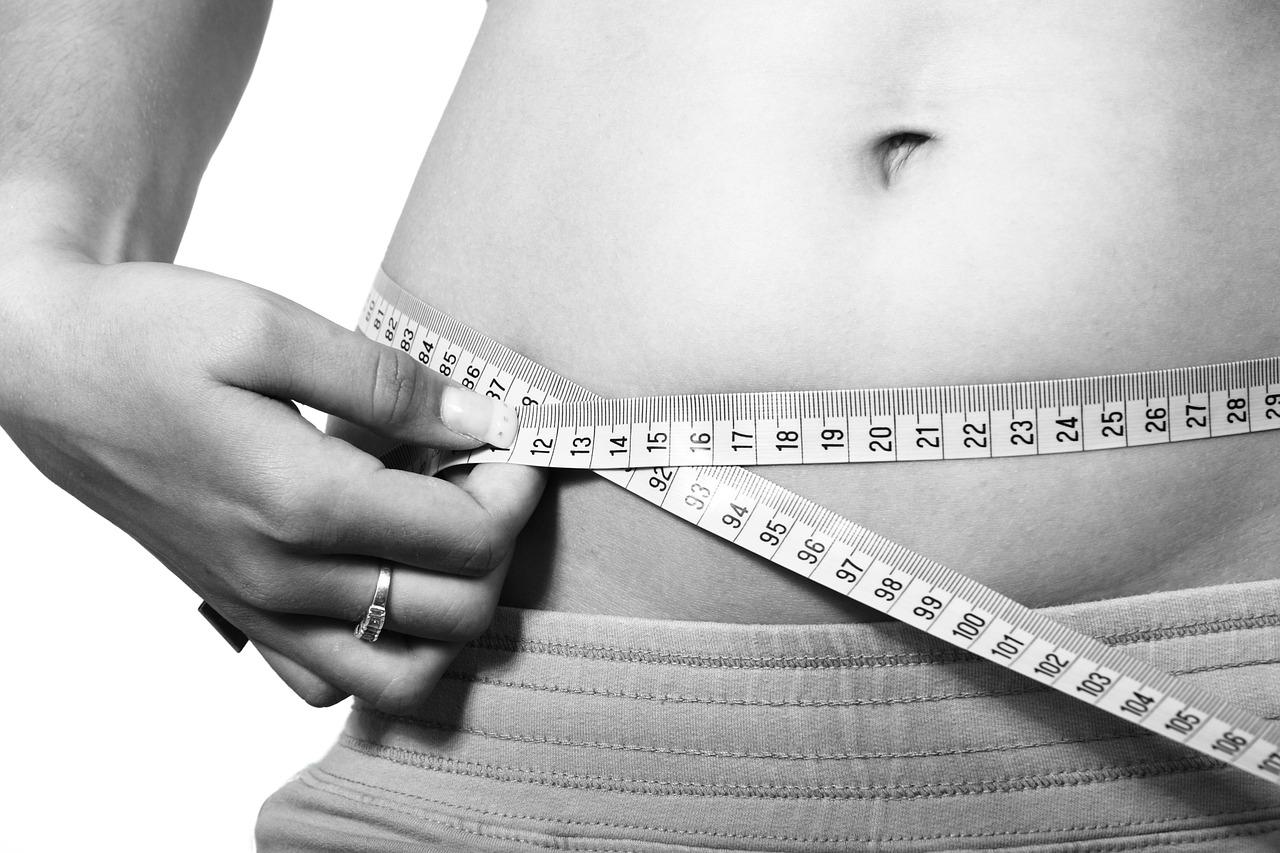 Zdjęcie ilustracyjne: brzuch kobiecy i centymetr; leczenie nadwagi