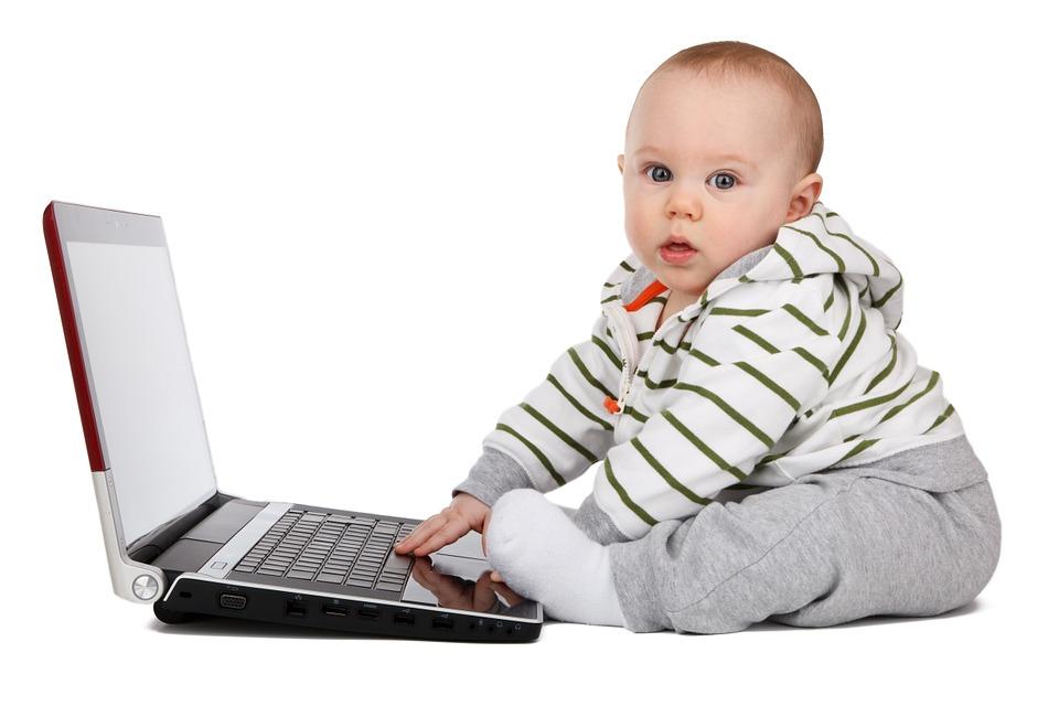 Niemowlę siedzi przy komputerze