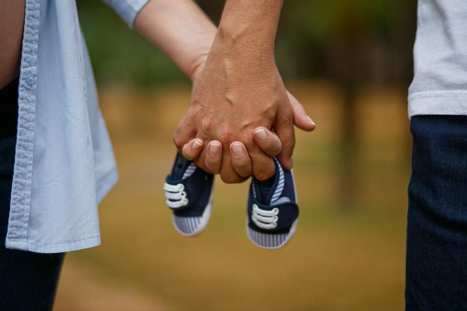 Para trzyma w dłoniach dziecięce buciki