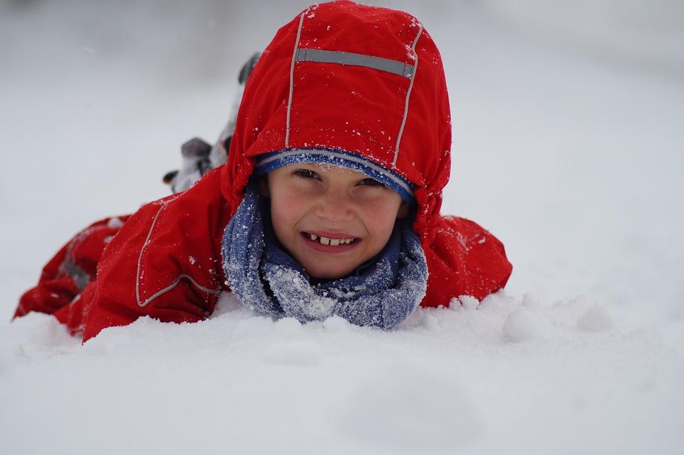 Chłopiec bawi się w śniegu