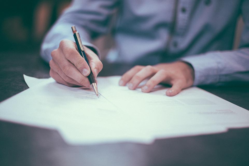 Mężczyzna skladający podpis pod dokumentem