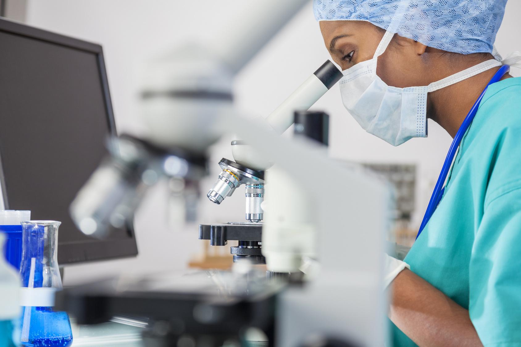 Kobieta w laboratorium sprawdza próbkę pod mikroskopem