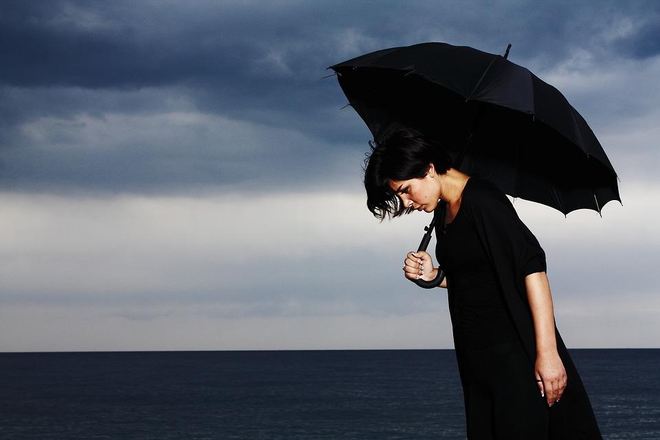 Smutna kobieta z czarnym parasolem /Ilustracja do tekstu: Depresja a szanse na ciążę. Czy depresja ma wpływ na płodność?