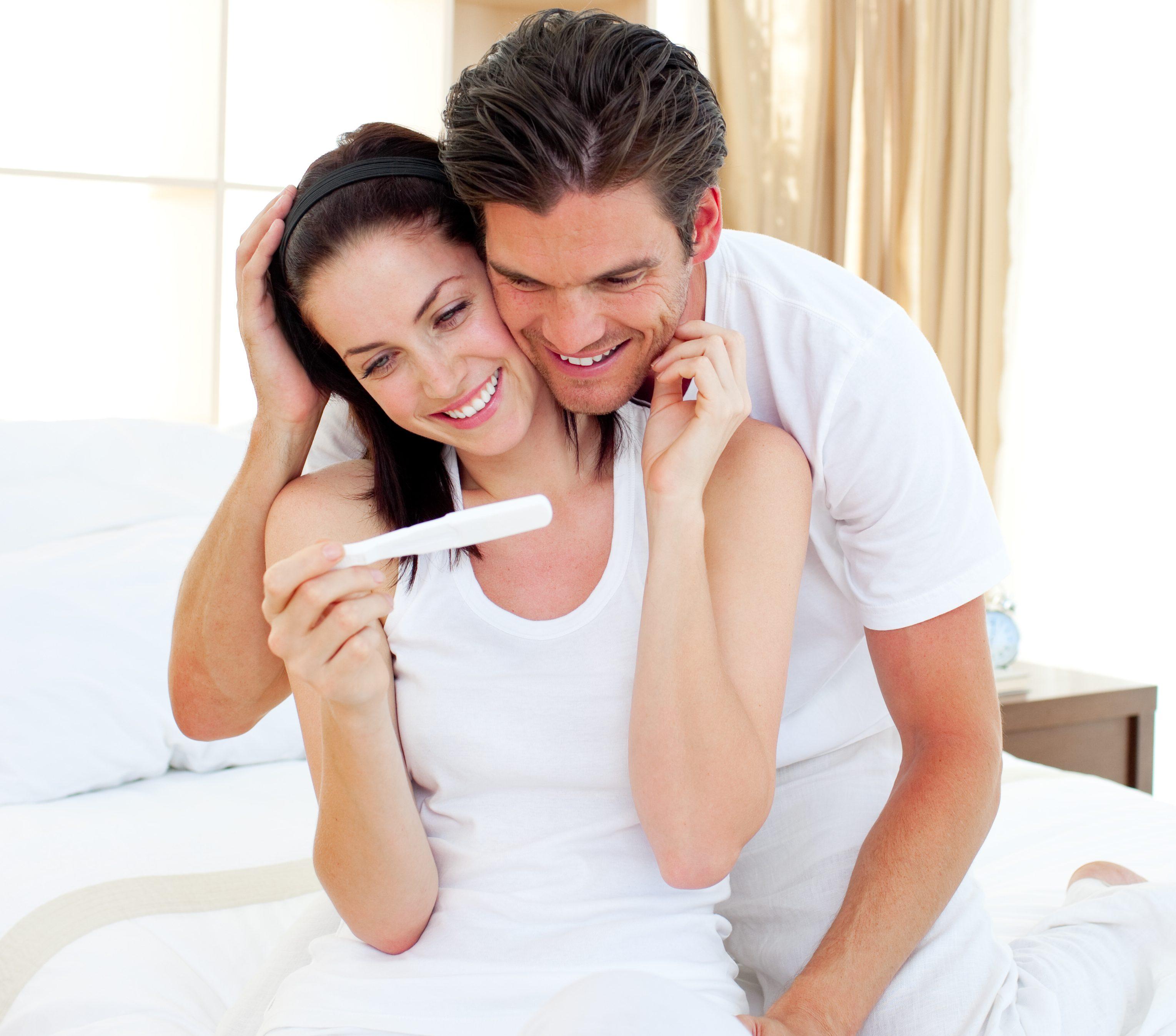 Uśmiechnięta para ogląda wynik testu ciążowego /Ilustracja do tekstu: Mezoterapia jajników. Jak działa i komu może pomóc?