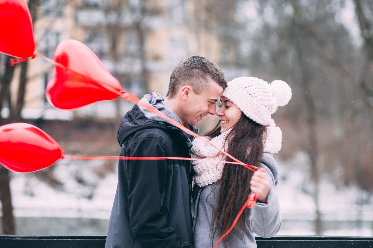 Przytulona para, która trzyma balon w ksztalcie serca
