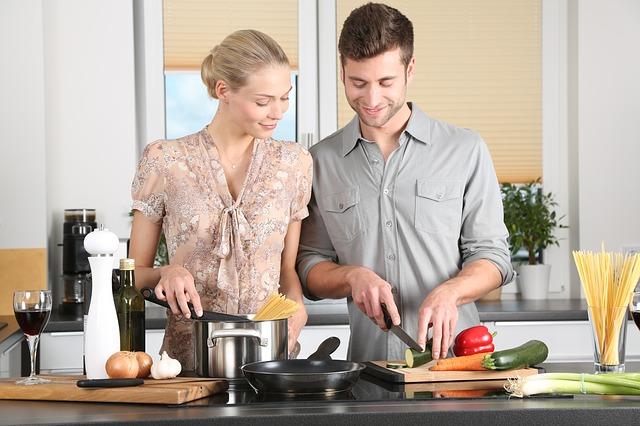 Para wspólnie przygotowująca posiłek w kuchni