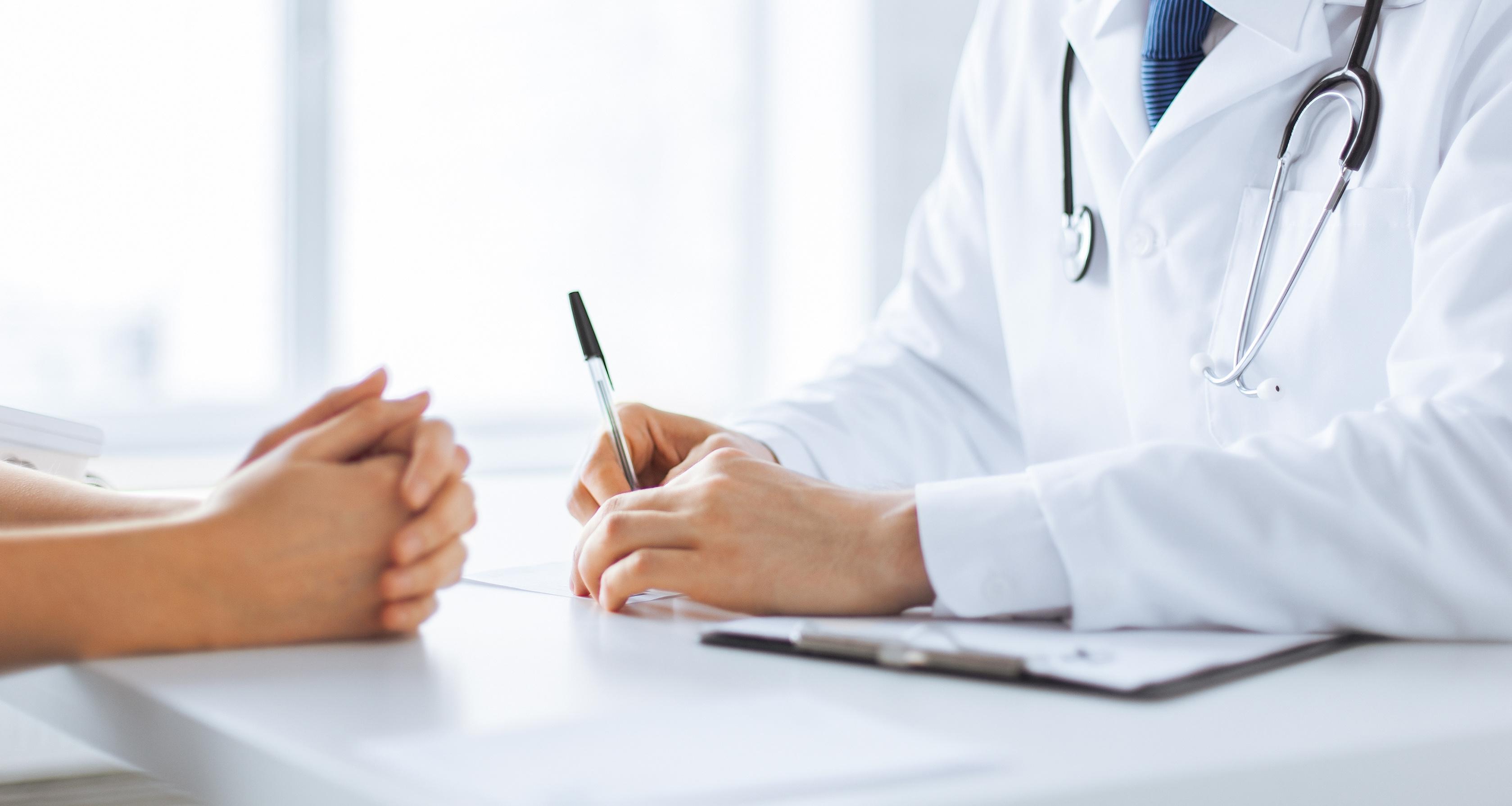 W kadrze widzimy ręce kobiety na biurku lekarskim, naprzeciwko lekarz.