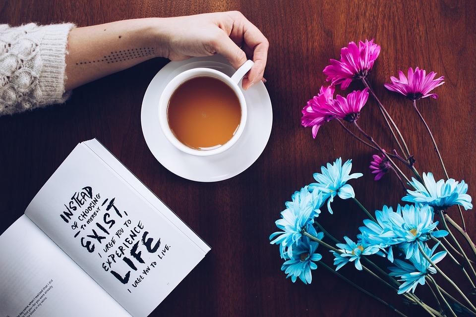 Kobieca dłoń obemuje filiżankę z kawą, obok kolorowe kwiaty i książka z motywcyjnym cytatem /Ilustracja do tekstu: Wirtualne wsparcie po diagnozie MRKH