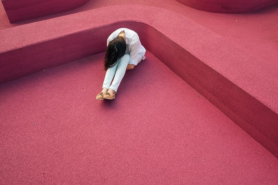Skulona kobieta na czerwonych schodach/ Ilustracja do tekstu: Endometrioza: objawy niedostrzegane przez lekarzy. Historie pacjentek
