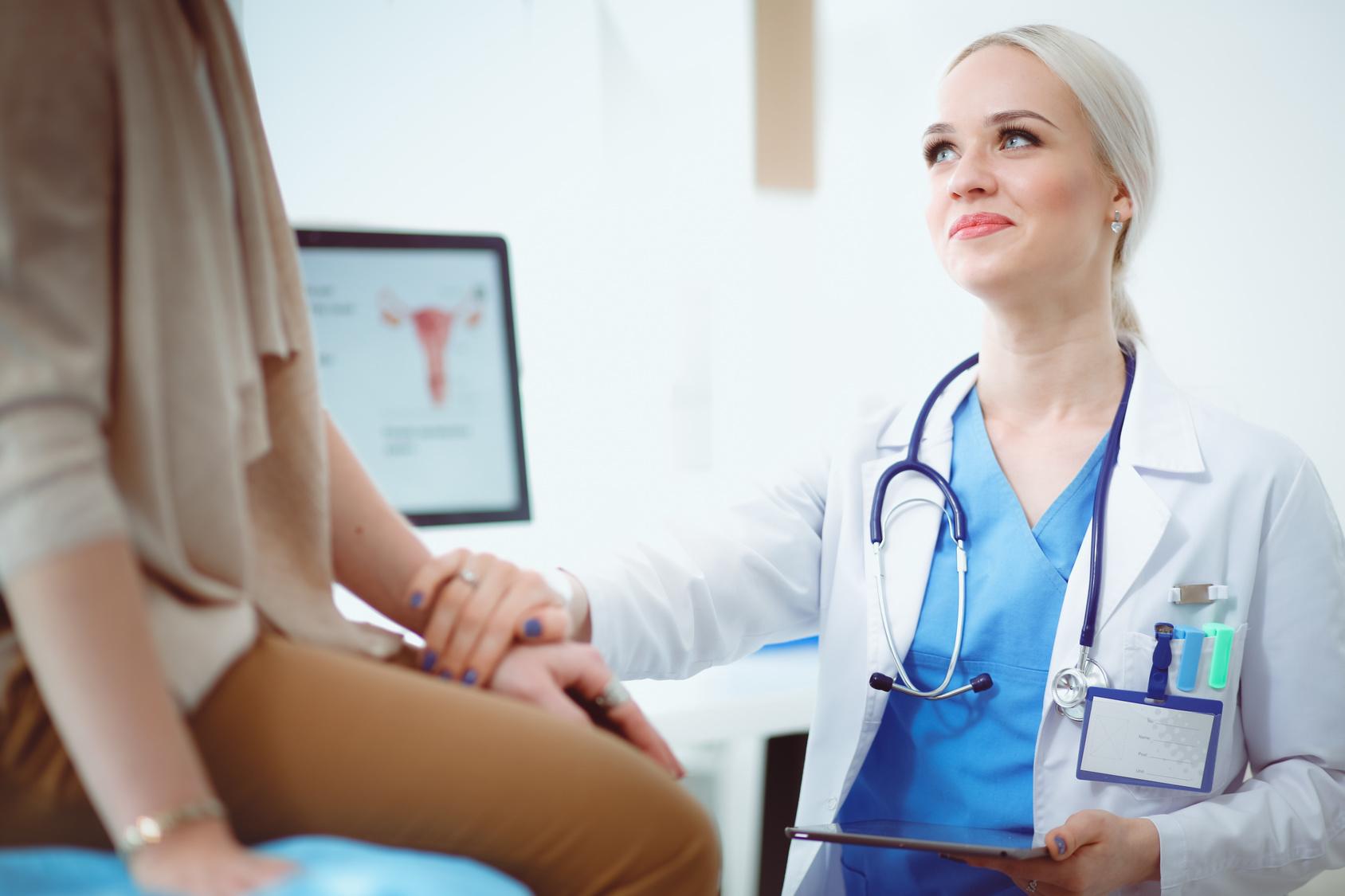 uśmiechnięta lekarka kładzie dłoń na ręku pacjentki; w tle wynik badania macicy /Ilustracja do tekstu: Innowacyjne leczenie endometriozy