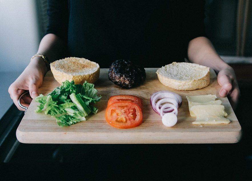 Drewniana deska w kobiecych dłoniach. Na niej: warzywa i pszenna bułka / Ilustracja do tekstu: Celiakia a płodność