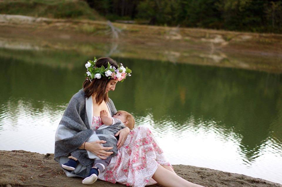 Młoda mama, ubrana w sukienkę i wianek, karmi dziecko piersią nad jeziorem. /Ilustracja do tekstu: Dziecięce body zachęci do karmienia piersią
