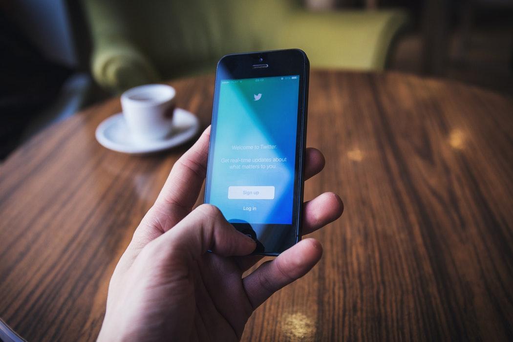 Smartfon w męskiej dłoni, na nim: logowanie na Twittera. /Ilustracja do tekstu: Ksiądz przestrzega przed Jackiem Jaśkowiakiem