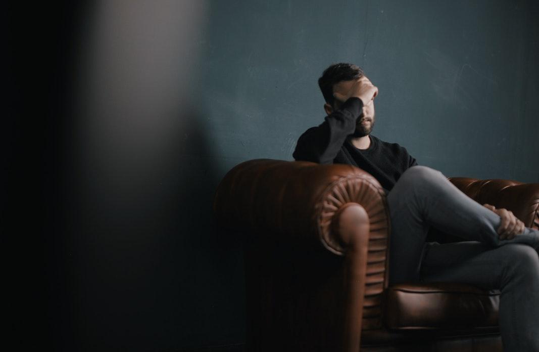 Zmartwiony mężczyzna na kanapie. Zakrywa twarz dłonią /Ilustracja do tekstu: Depresja a niepłodność męska /Żałoba mężczyzny po poronieniu