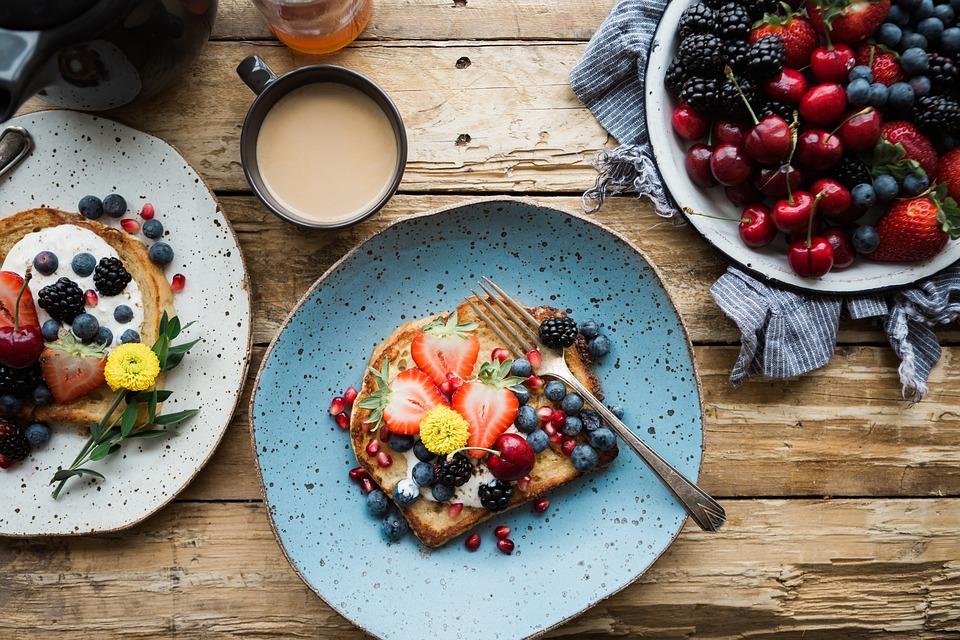 Talerz z kolorową kanapką, wokół naczynia ze świeżymi owocami / Ilustracja: fast food, Owoce a płodność. Naukowcy sprawdzili, jak dieta wpływa na zajście w ciążę