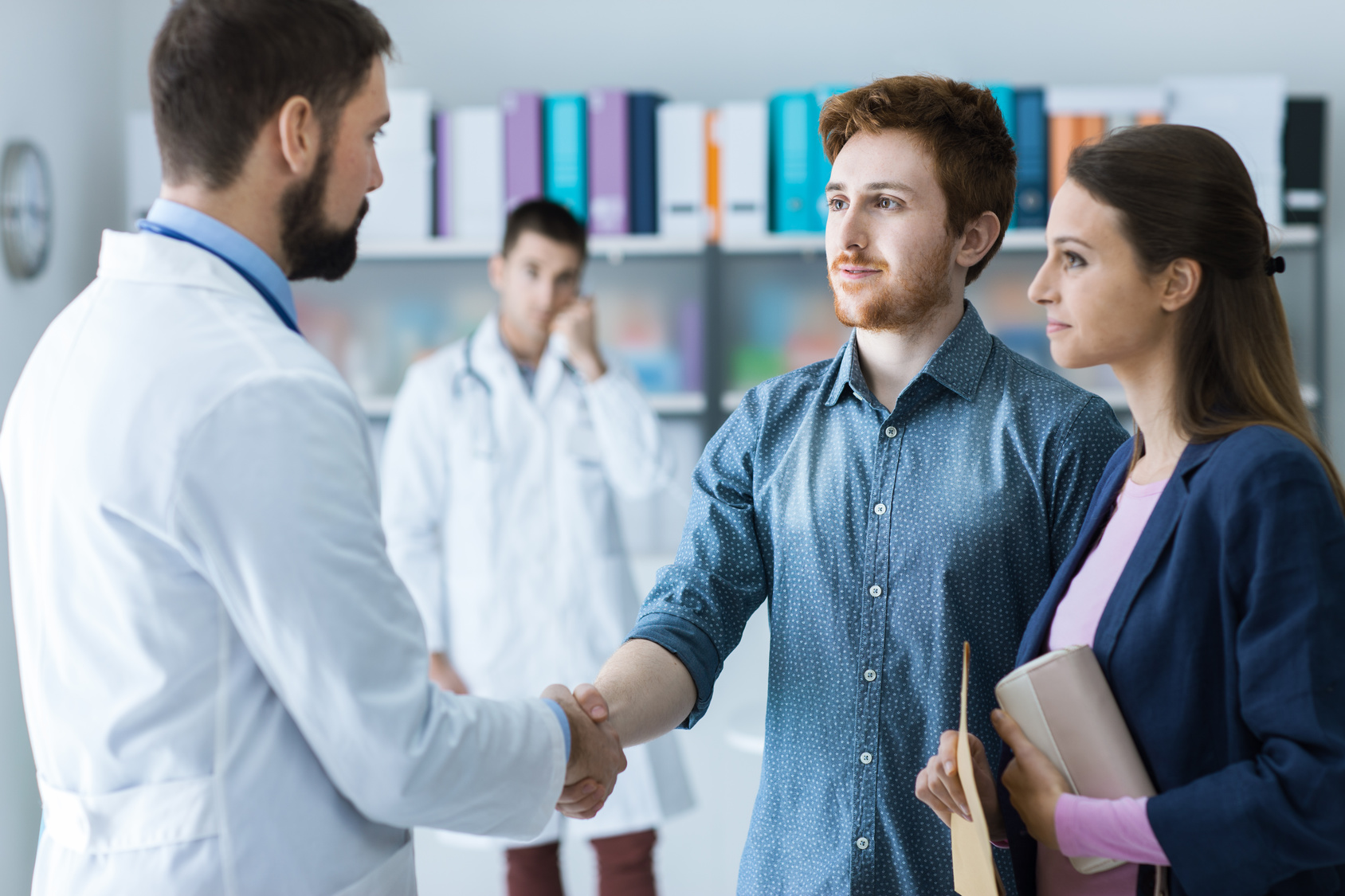 Para w gabinecie lekarskim. Lekarz podaje dłoń mężczyźnie /Ilustracja do tekstu: Pierwsza wizyta w klinice leczenia niepłodności