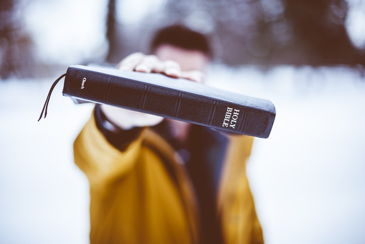 Mężczyzna pokazuje Biblię do obiektywu /Ilustracja do tekstu: Dofinansowanie in vitro w Kołobrzegu zagrożone? Kościół straszy wiernych
