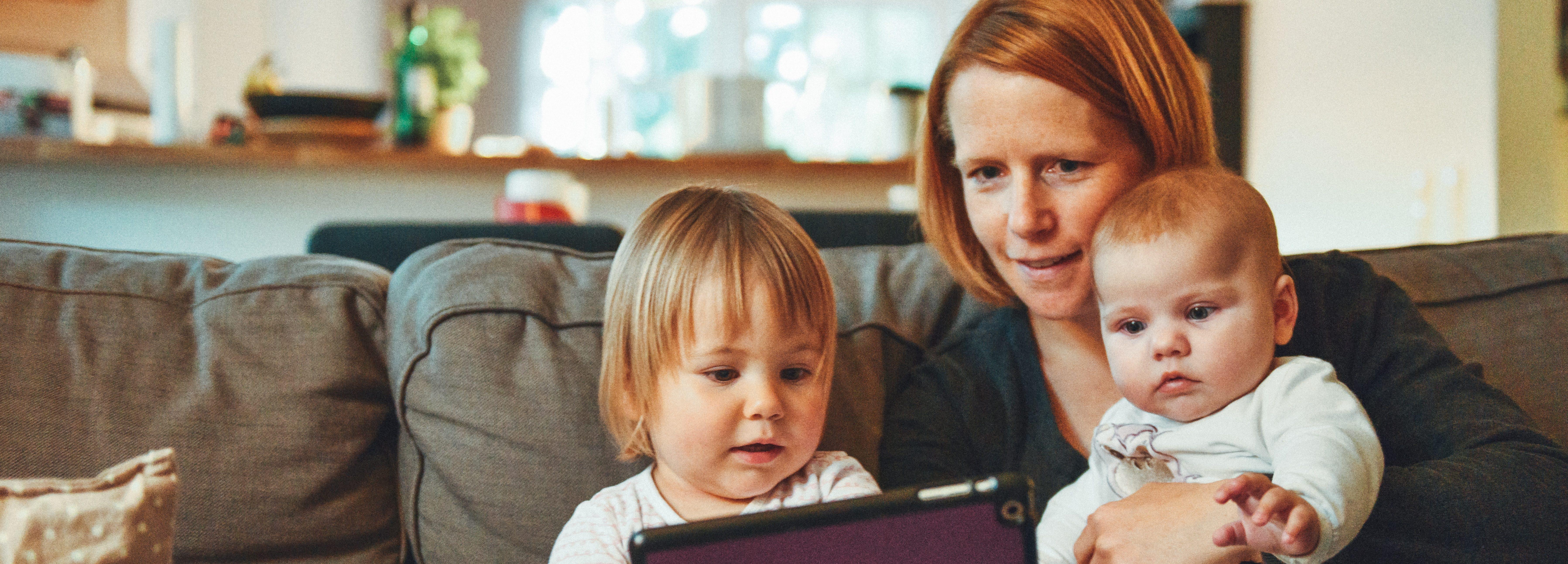Mama pokazuje tablet dwójce dzieci /Ilustracja do tekstu: Dzieci z in vitro: co sądzą o swojej metodzie poczęcia?