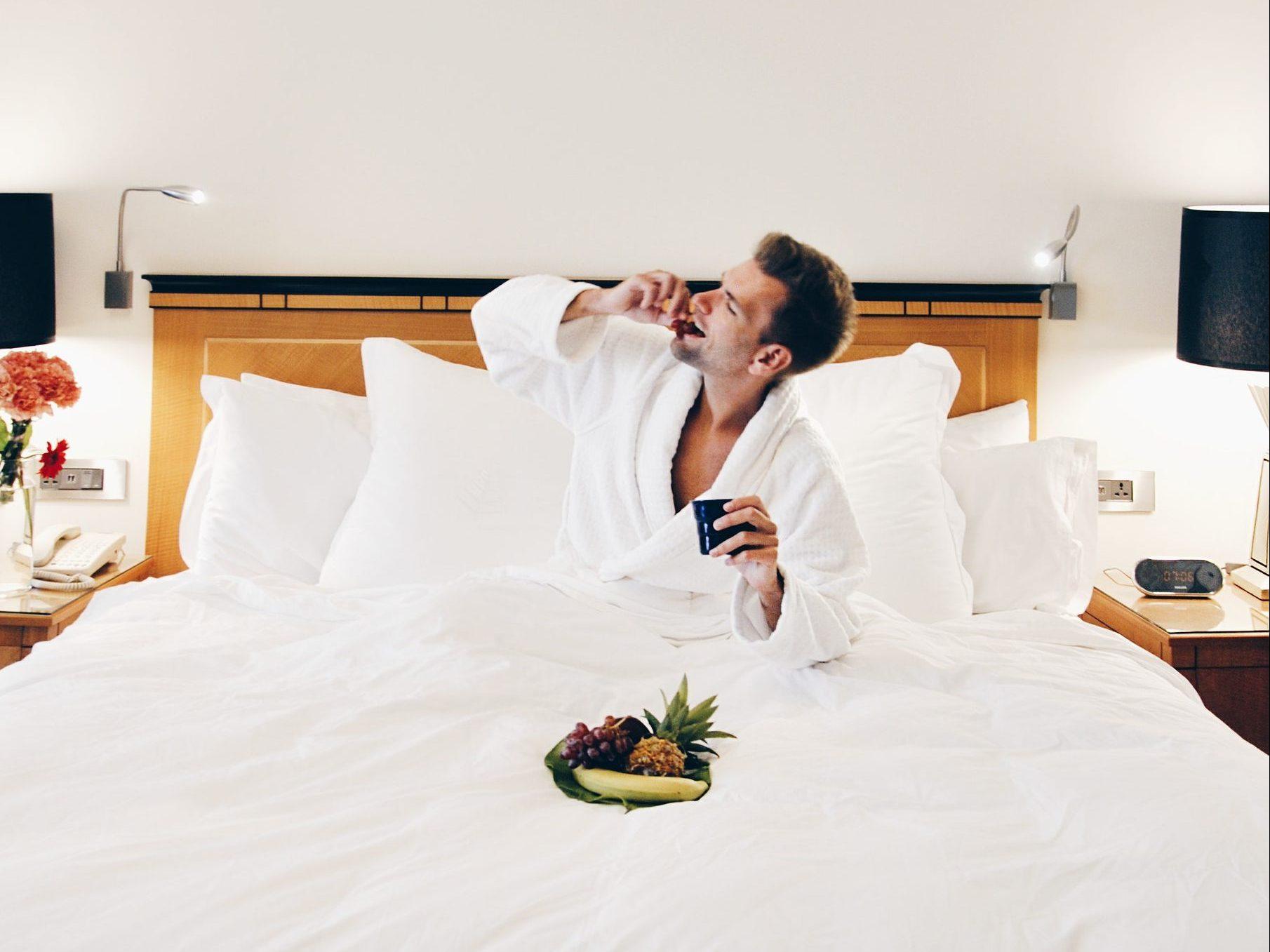 Szczęśliwy mężczyzna pije kawę w hotelowym łóżku. Przed nim talerz z owocami /Ilustracja do tekstu: Zadbaj o jakość nasienia latem