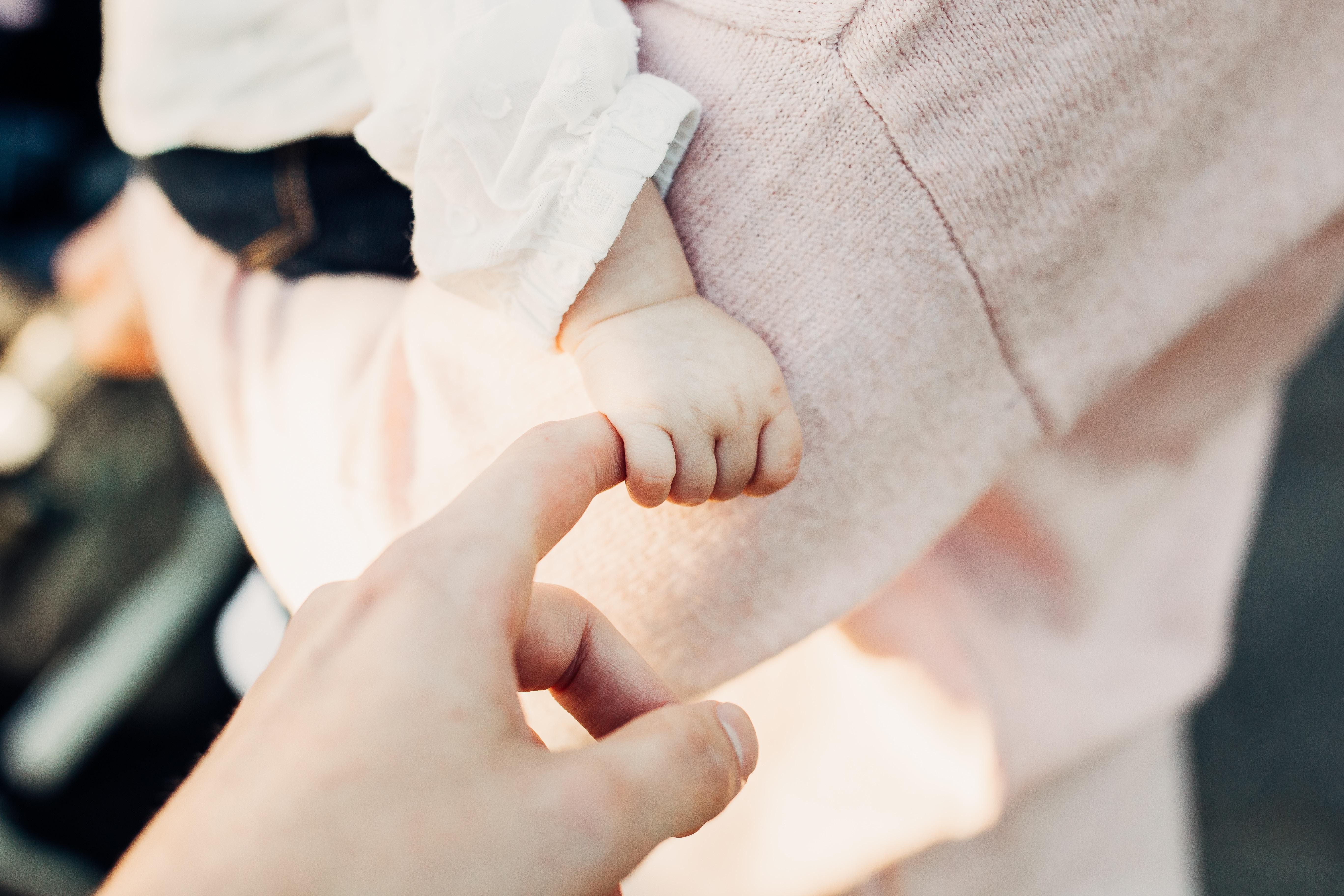 Niemowlę na rękach mamy; trzyma tatę za palec /Ilustracja do tekstu: Bon opiekuńczy: wieloraczki - nowe świadczenie dla rodziców