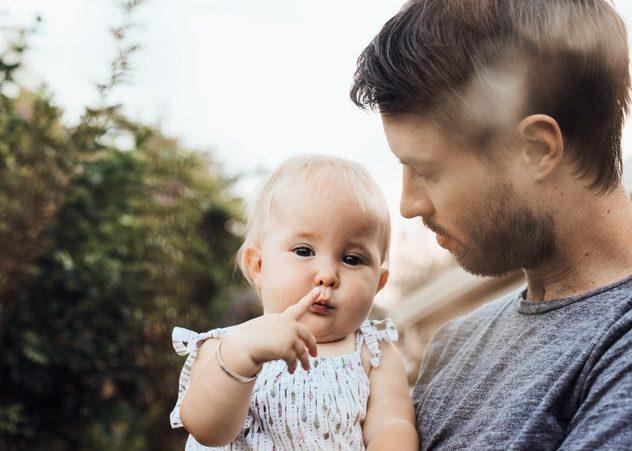 Tata trzyma na rękach małą córeczkę /Ilustracja do tekstu: Tato, wspieraj mamę! O roli ojca w czasie ciąży i porodu oraz po porodzie