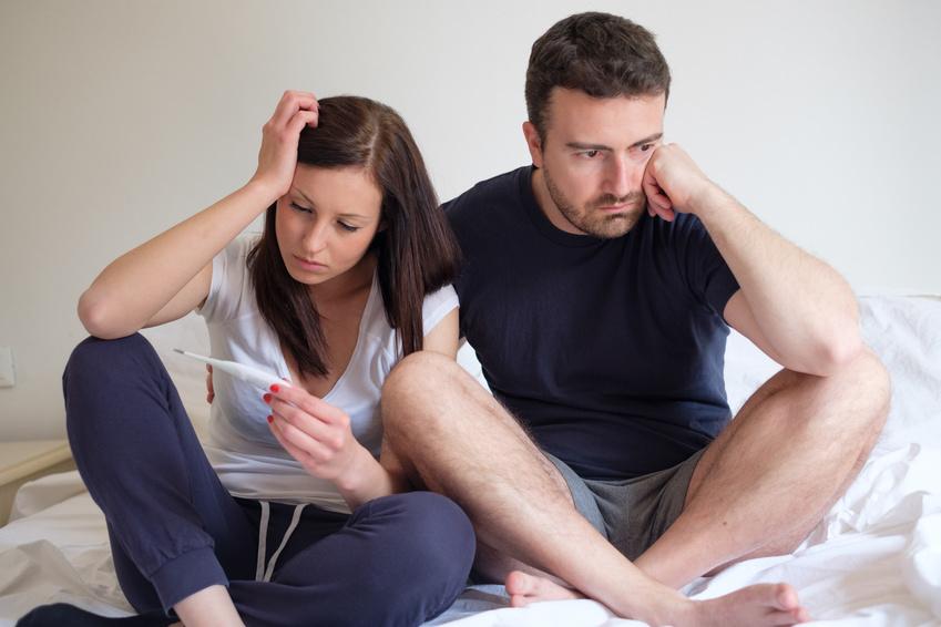Smutna para w łóżku; kobieta trzyma w dłoni test ciążowy /Ilustracja do tekstu: Program prokreacyjny okazał się fiaskiem. wszystko przez procedury?