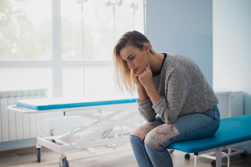dlaczego kobiety mrożą jajeczka /Na zdjęciu: Smutna kobieta siedzi na brzegu łóżka