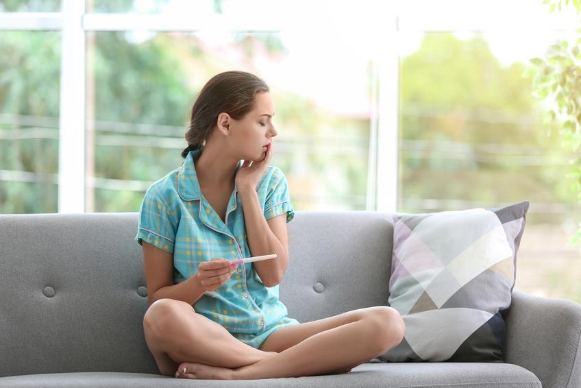 Smutna kobieta siedzi na kanapie z testem ciążowym w dłoni /Ilustracja do tekstu: Ciąża biochemiczna: czym jest?