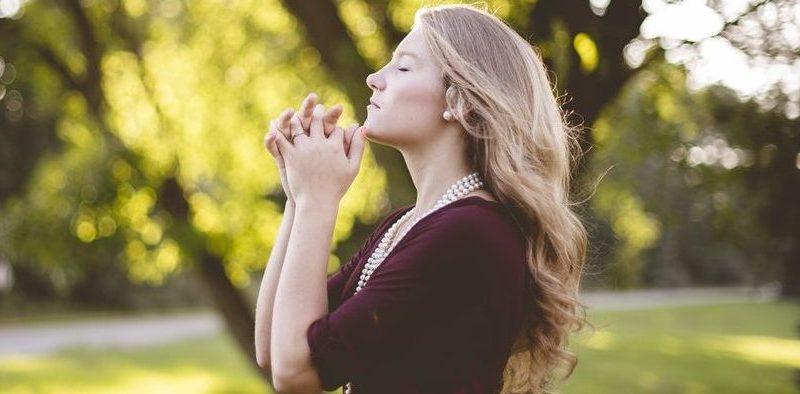 Ilustracja do tekstu: Afirmacje na płodność. Na zdjęciu: Młoda kobieta na łonie przyrody; z rękami złożonymi do modlitwy