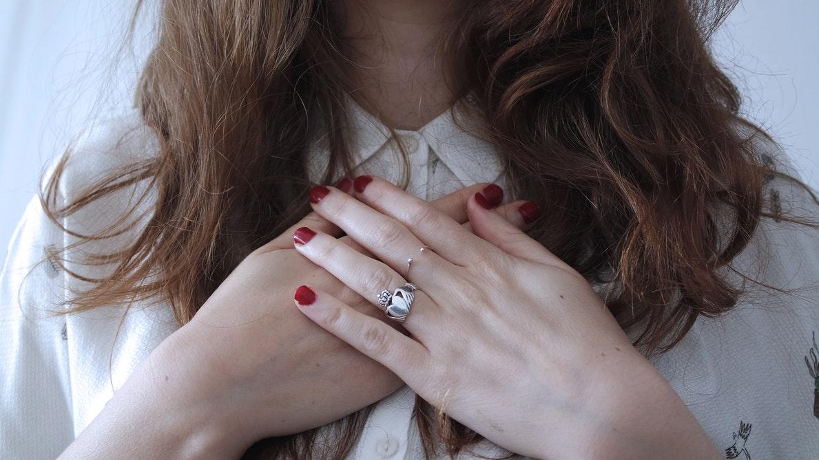 Kobieta układa ręce na sercu /Ilustracja do tekstu: wysoki cholesterol a ciąża. Niepłodność i choroby serca mogą mieć to samo podłoże