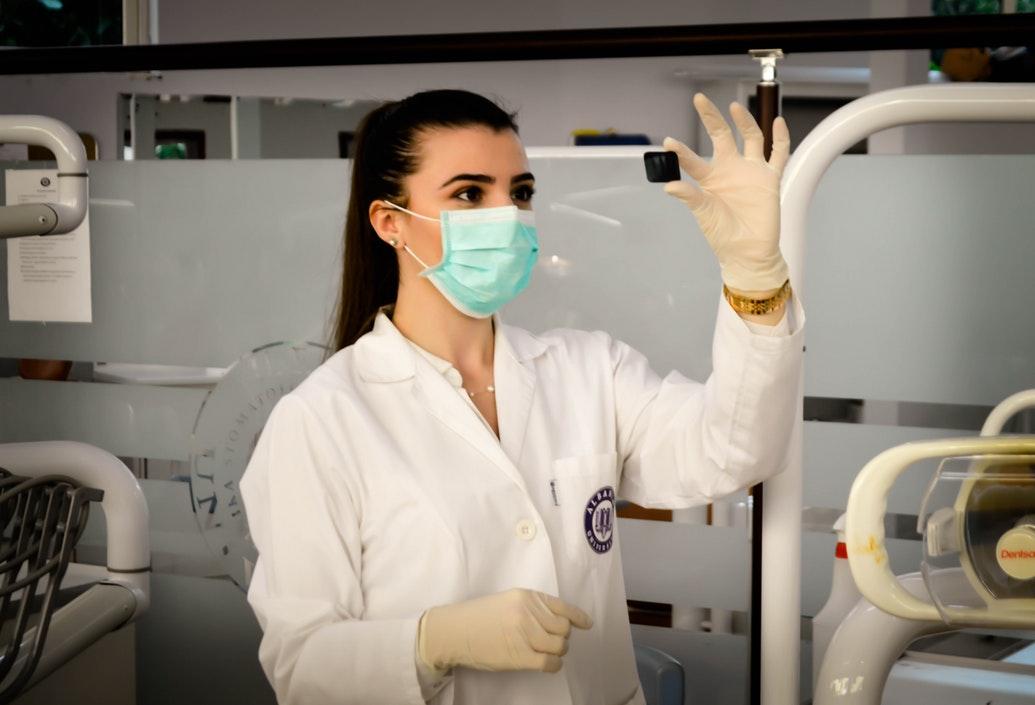 Technik w laboratorium. W ręku trzyma próbkę /Ilustracja do tekstu: Przełomowe odkrycia w embriologii. Stoi za nimi Polka
