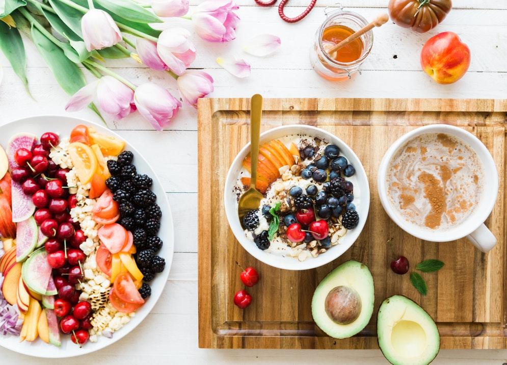 Dietetyczne produkty spożywcze estetycznie podane w miseczkach: owsianka z owocami, połówki awokado /Ilustracja do tekstu: Dieta na owulację przy PCOS