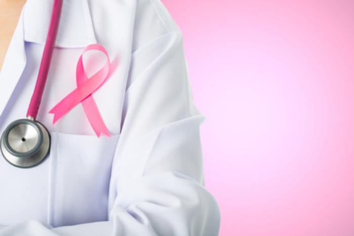 Lekarz z różową wstążka przypiętą do kitla /Ilustracja do tekstu: Ciąża po raku piersi: szanse, zagrożenia. Leczenie raka a płodność, metody zachowania płodności