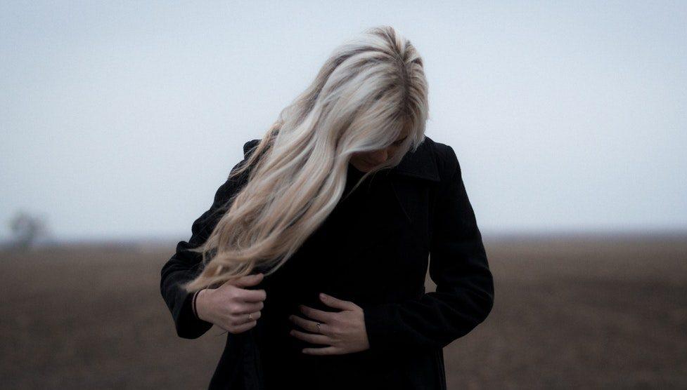 Kobieta w płaszczu dotyka z troską swojego brzucha /Ilustracja do tekstu: Mity o niepłodności. Ty też je słyszysz?