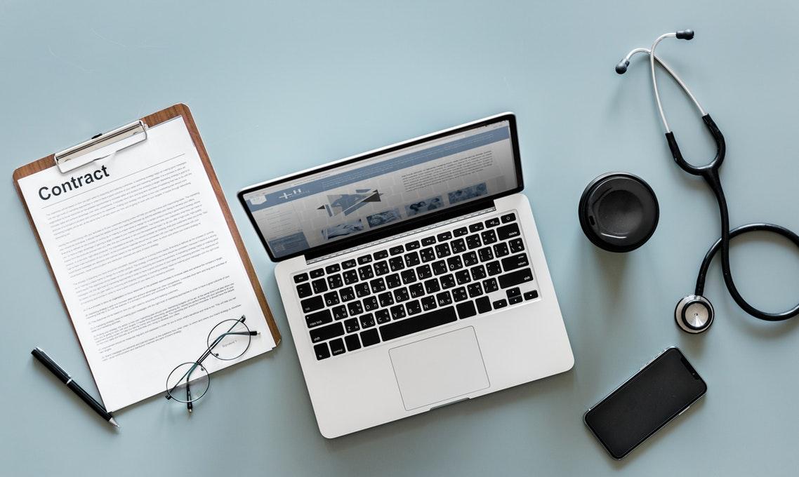 Dokumentacja medyczna na komputerze, obok: stetoskop, kontrakt medyczny /Ilustracja do tekstu: Internetowe Konto Pacjenta umożliwi dostęp do historii medycznej i recept za jednym kliknięciem?