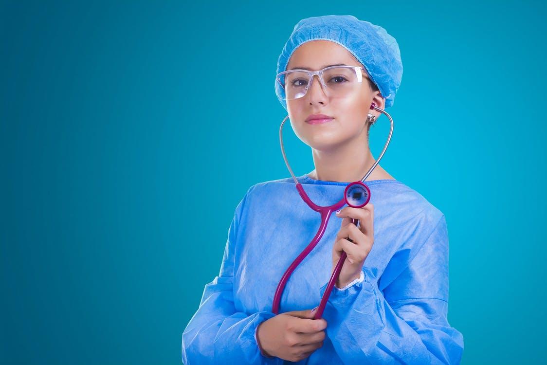 Dobry specjalista od endometriozy. 10 wskazówek, jak go znaleźć /Na zdjęciu widzimy: Młoda lekarka w niebieskim kitlu, czepku i okularach, z czerwonym stetoskopem w dłoni