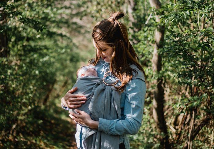 Uśmiechnięta mama z dzieckiem w chuście. Ilustracja do tekstu: Karmienie piersią w różnych krajach: w Polsce i na świecie