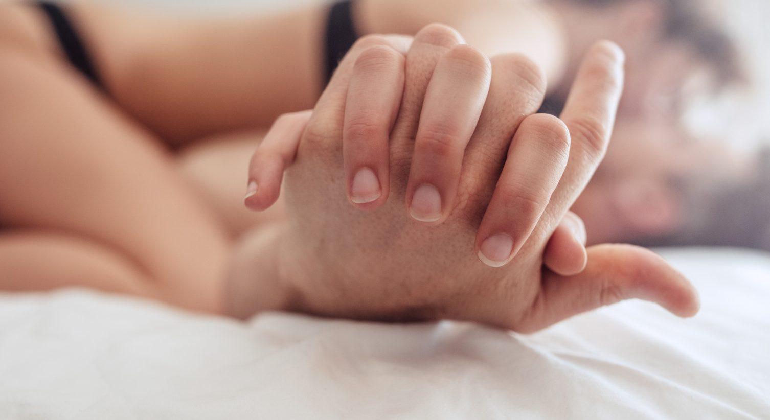 Para na łóżku; na pierwszym planie złączone dłonie Ilustracja do tekstu: Seks a niepłodność / Seks po operacji ginekologicznej