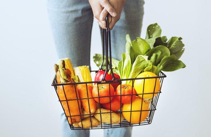 Letnie superfoods na płodność /Na zdjęciu: Kobieta trzyma w dłoniach sklepowy koszyk wypełniony warzywami i owocami (marchew, cytryny, pomarańcze, warzywa liściaste)