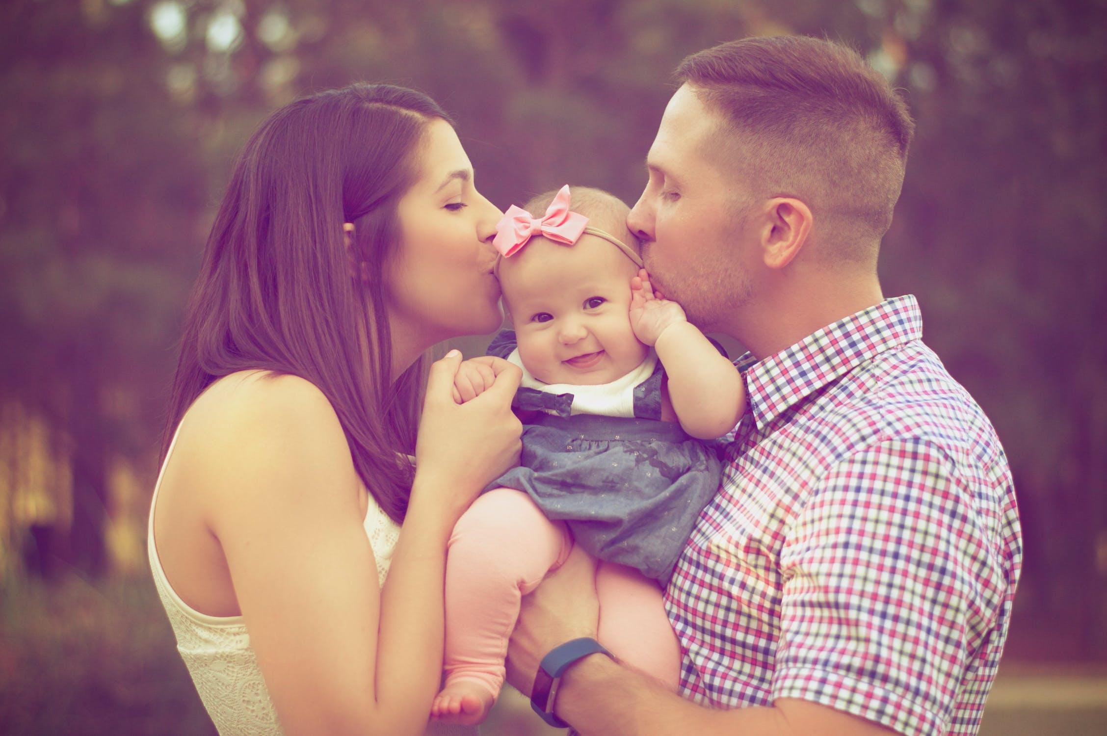 Program dofinansowania in vitro w Warszawie przyniósł rodzicom szczęście /Na zdjęciu: Rodzice całują uśmiechniętą małą dziewczynkę z różową kokardką