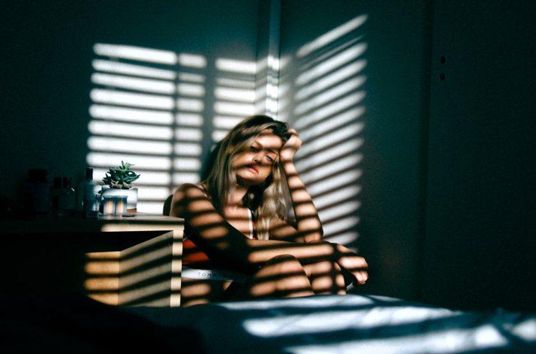 Celiakia a przedwczesna menopauza /Na zdjęciu: Smutna kobieta siedzi na łóżku w zacienionym pokoju